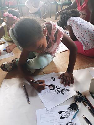 Niña afrocolombiana colorea dibujos afro